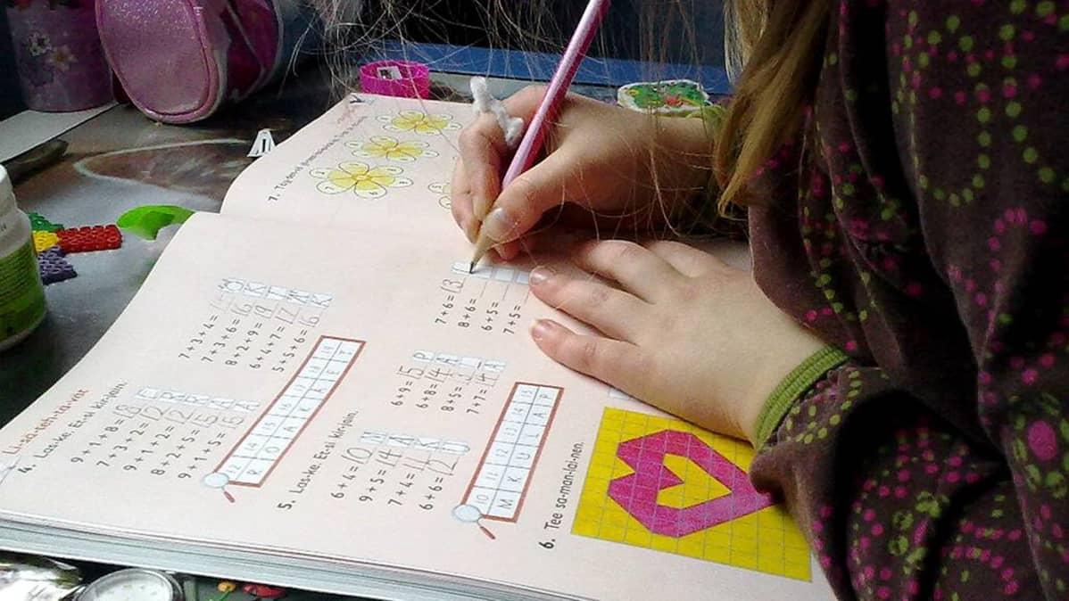 Koululainen tekee matematiikan tehtävää.