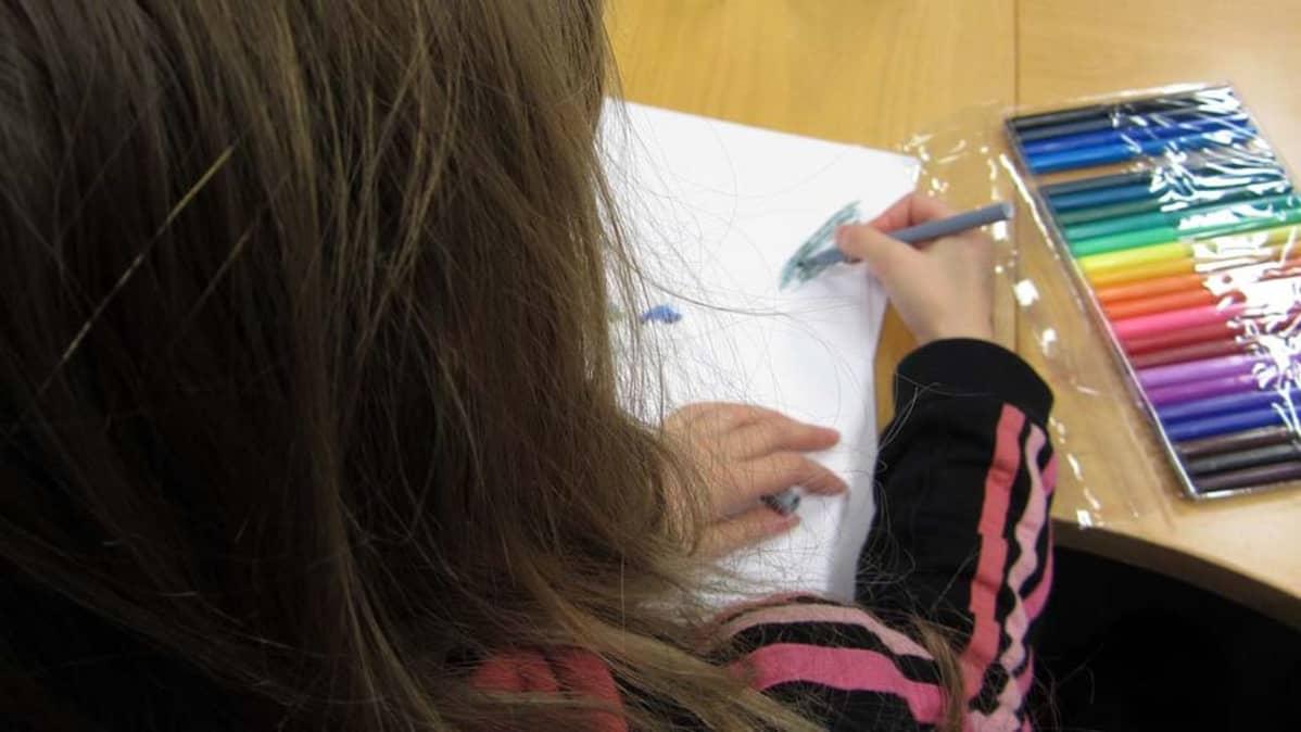 Kuvassa tyttö piirtää tussikynillä