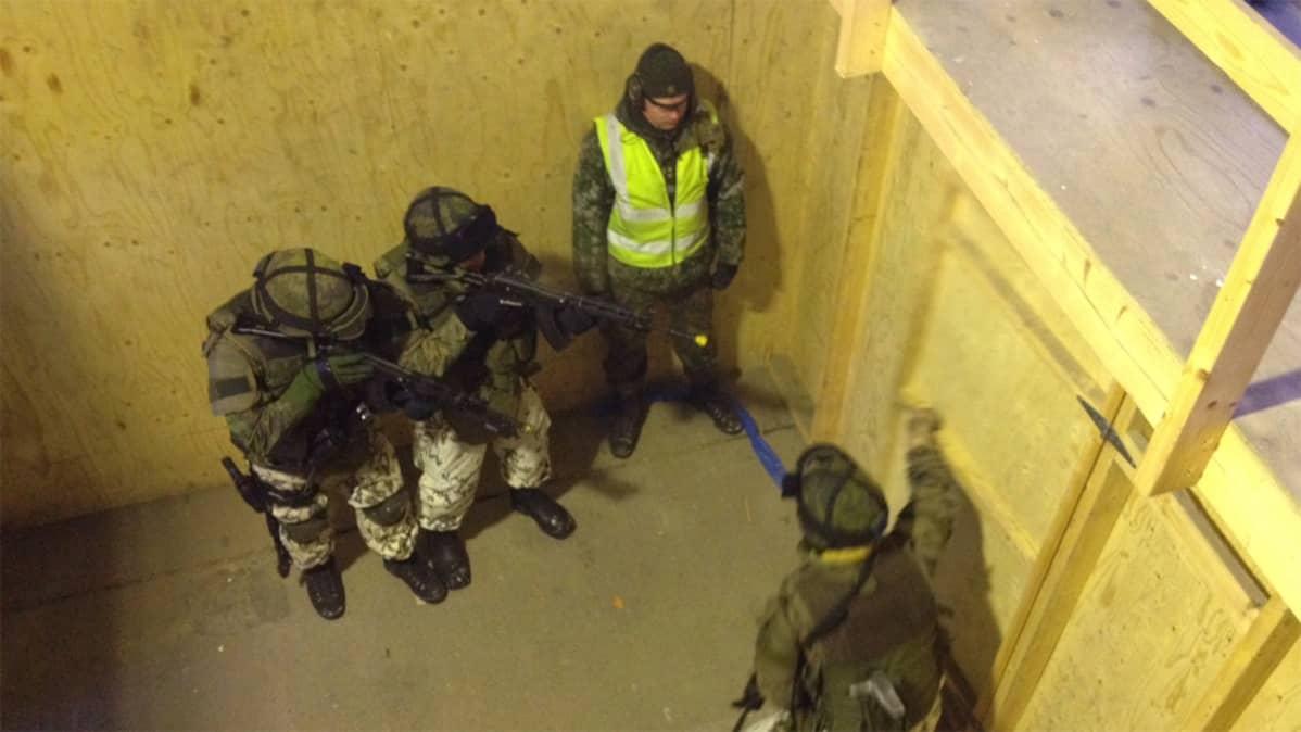Sotilaat osoittavat aseella ovea sotaharjoituksessa.