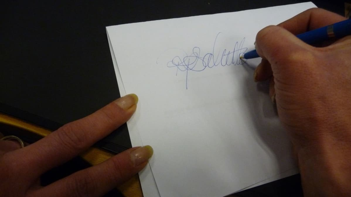 nainen kirjoittaa allekirjoitusta