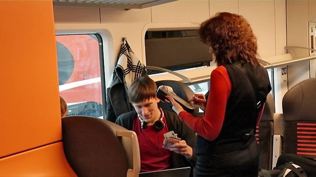 Nuori mies maksaa junalippuansa junassa naiskonduktöörille.