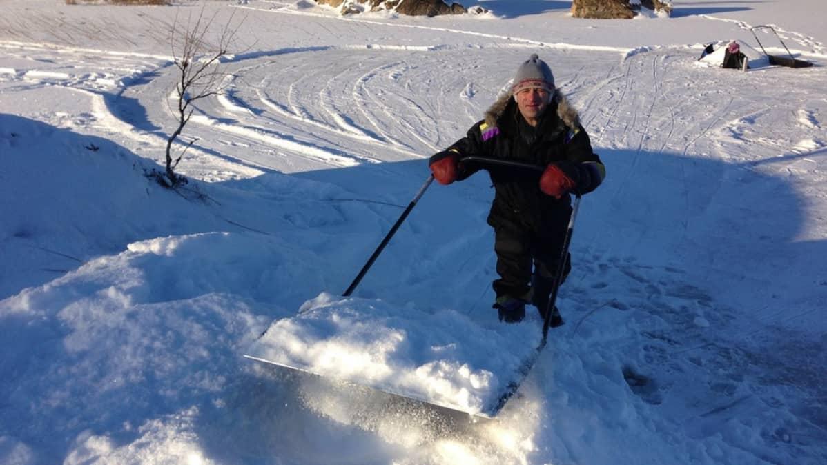 Metsähallituksen suojelubiologi Jouni Koskela kasaa lunta apukinokseen.