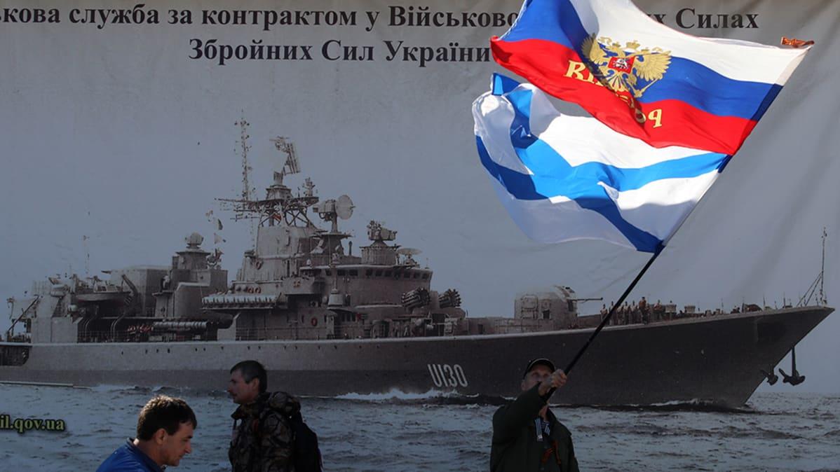 Mies heiluttaa Venäjän lippua Ukrainan laivastotukikohdan lähettyvillä.