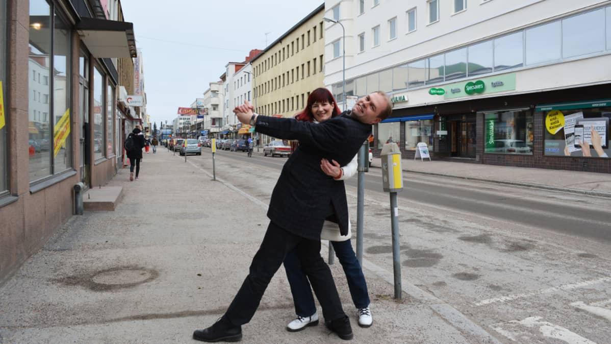 Kainuun Sanomien päätoimittaja Markus Pirttijoki taivuttelee tanssiopettaja Minna Palokankaan kanssa Kajaanin Kauppakadulla.