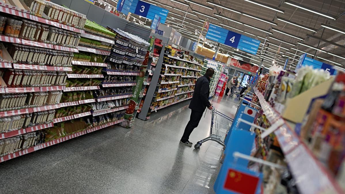 Asiakas työntää ostoskärryjä ruokakaupassa.