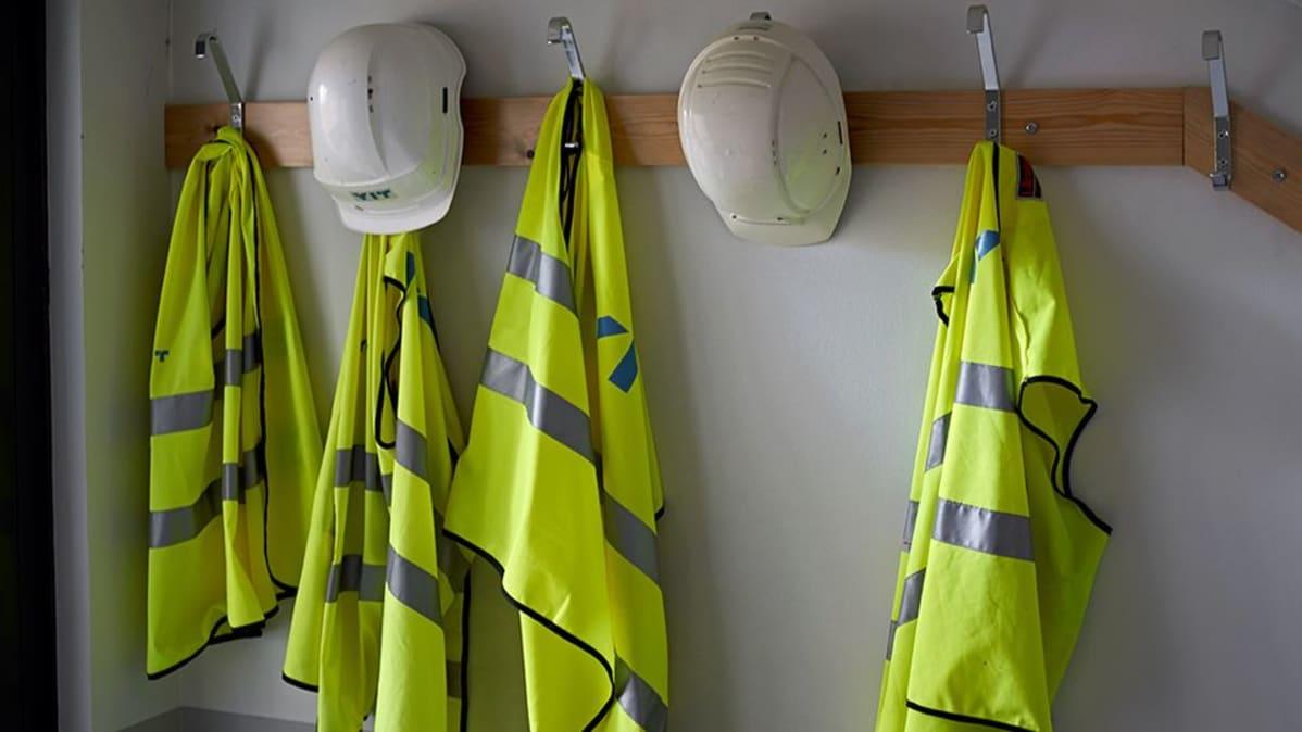 Turvaliivejä ja kypäröitä rakennustyömaan toimiston naulakossa.