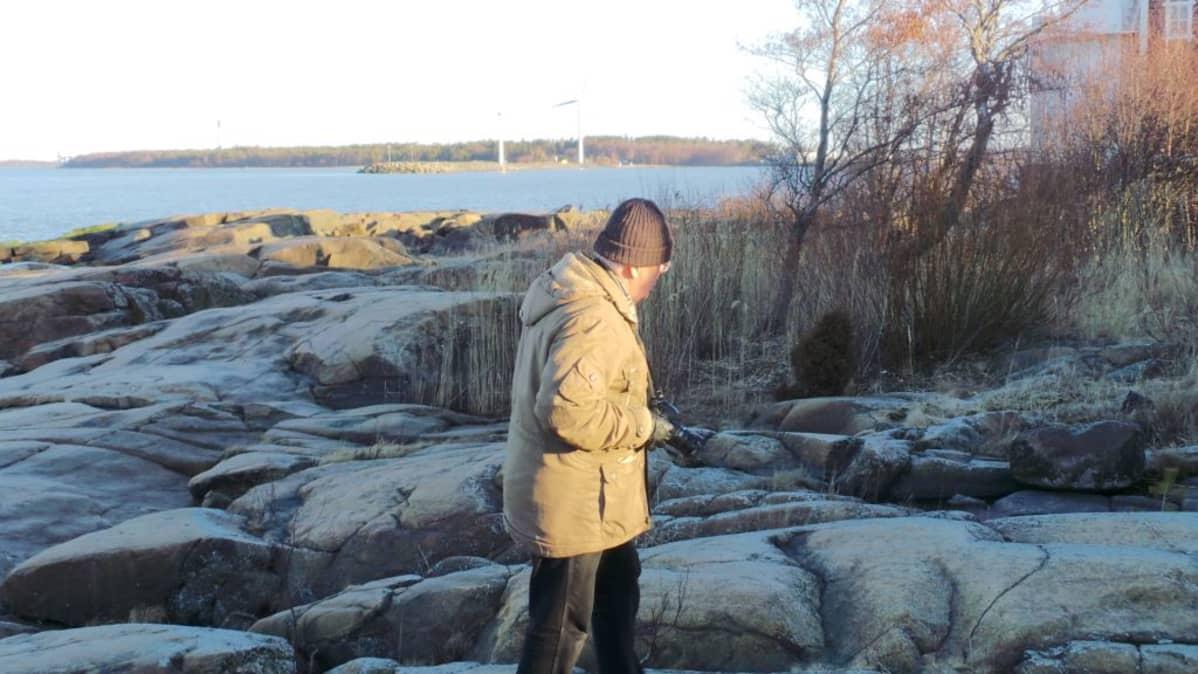 Pastori Hannu Salonoja tutkiskelee kallioihin raapustettuja muistomerkintöjä.
