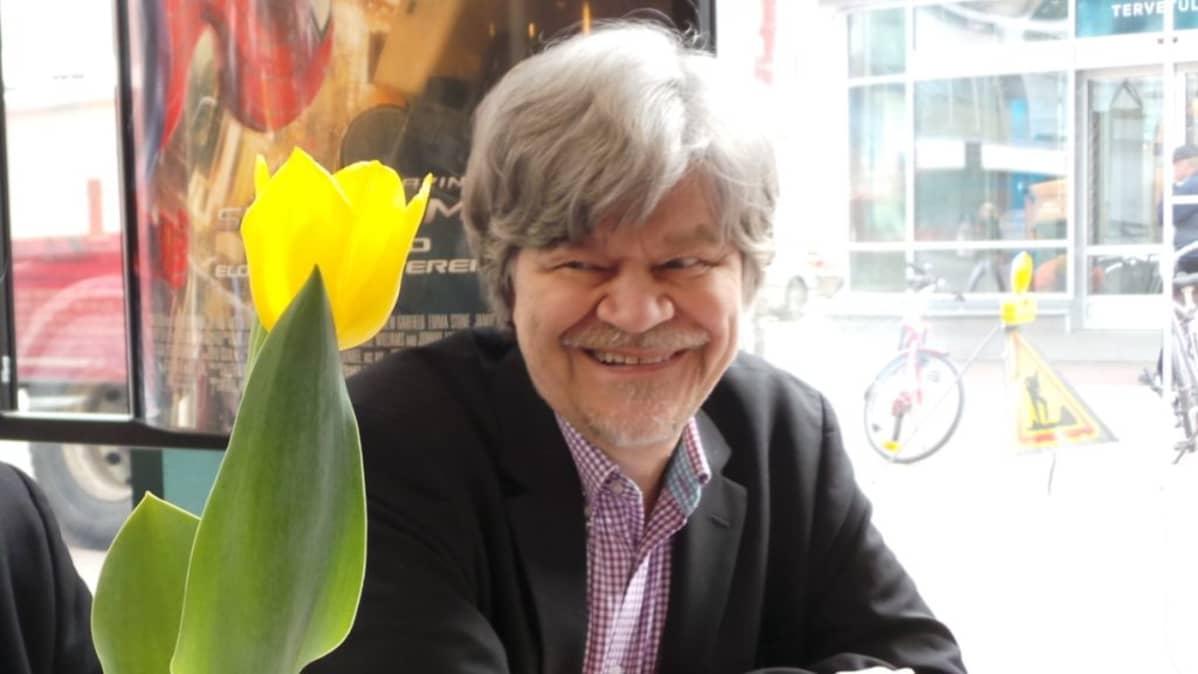 M.A. Numminen istuu pöydän ääressä.