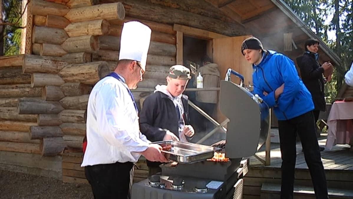 Päijät-Hämeen keittömestreiden puheenjohtaja Markku Ojala opastaa lapsia ruoanlaitossa.