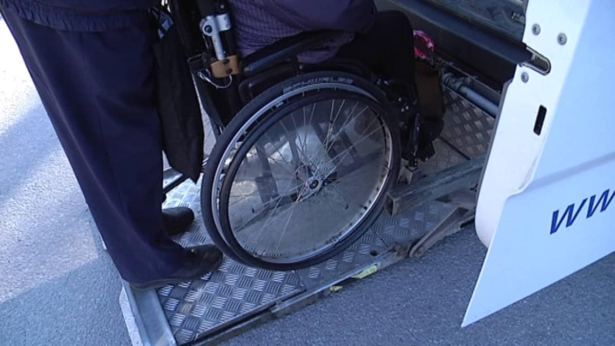 Pyörätuolia nostetaan taksin kyytiin.