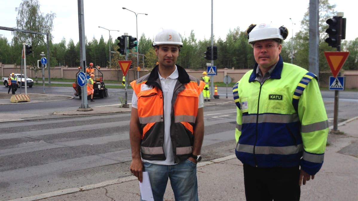 Työmaapäällikkö ja rakennuttajainsinööri kaupunkiasfalttityömaan äärellä