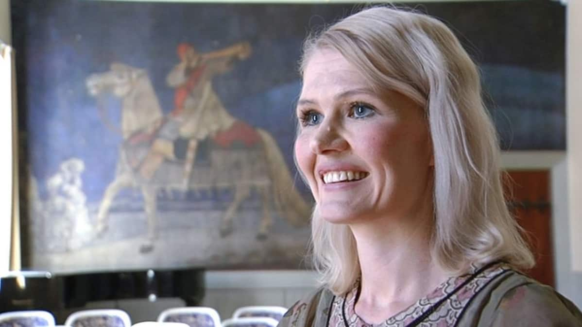 Historioitsija Jenni Kirves ja taustalla Akseli Gallen-Kallelan Kullervon sotaan lähtö -maalaus.