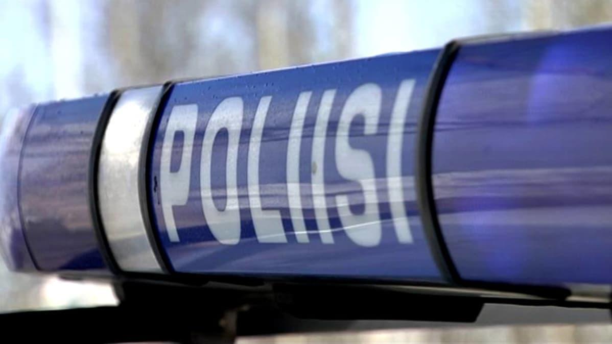 Poliisi-kyltti auton katolla.