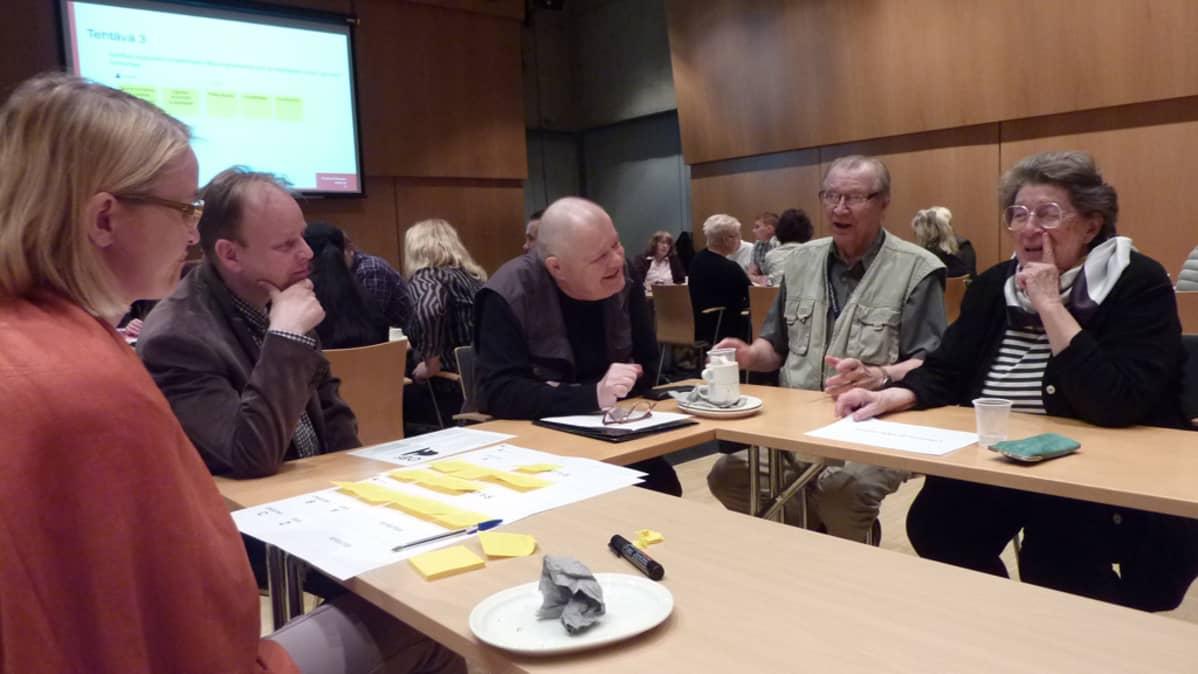 Ryhmä pohtii pöydän ympärillä tehtävää.