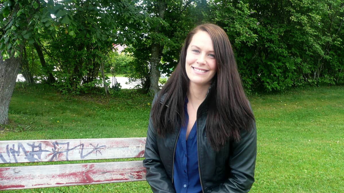 Nuori nainen istuu puistonpenkillä