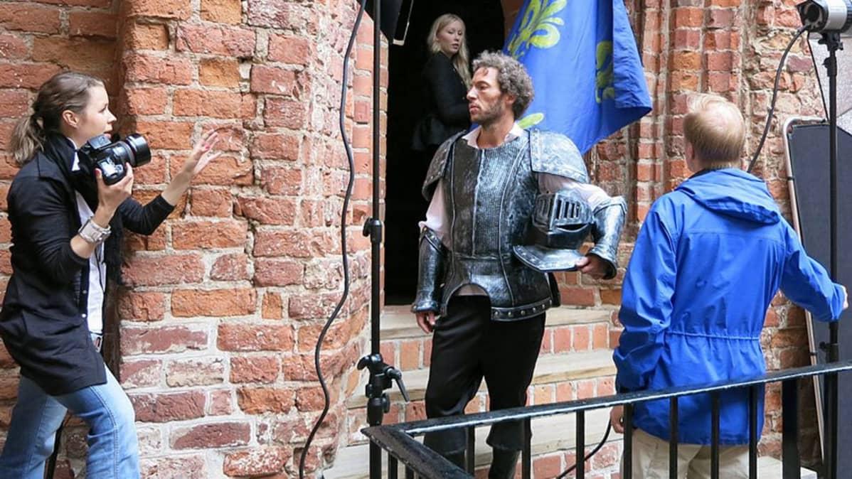 Kuvaaja Tiina Puputti antaa neuvoja kuvattavalle ritarille Hämeen linnassa.