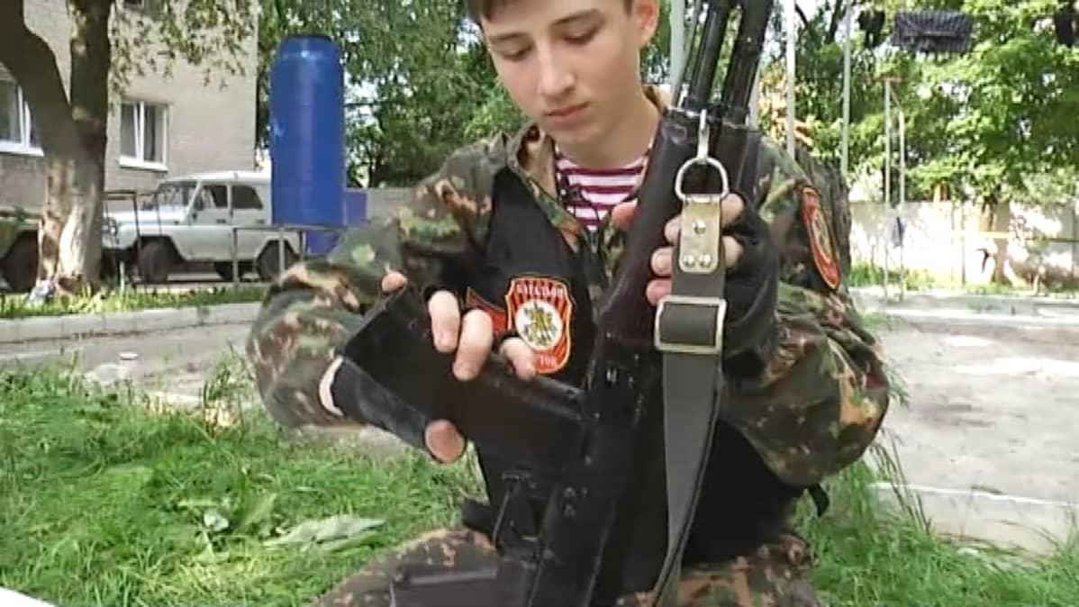 15-vuotias Andrei kouluttaa uusia separatistitaistelijoita mm. aseen käsittelyssä.