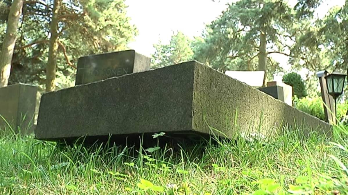 Kumottuja hautakiviä Hietaniemen uurnalehdossa.