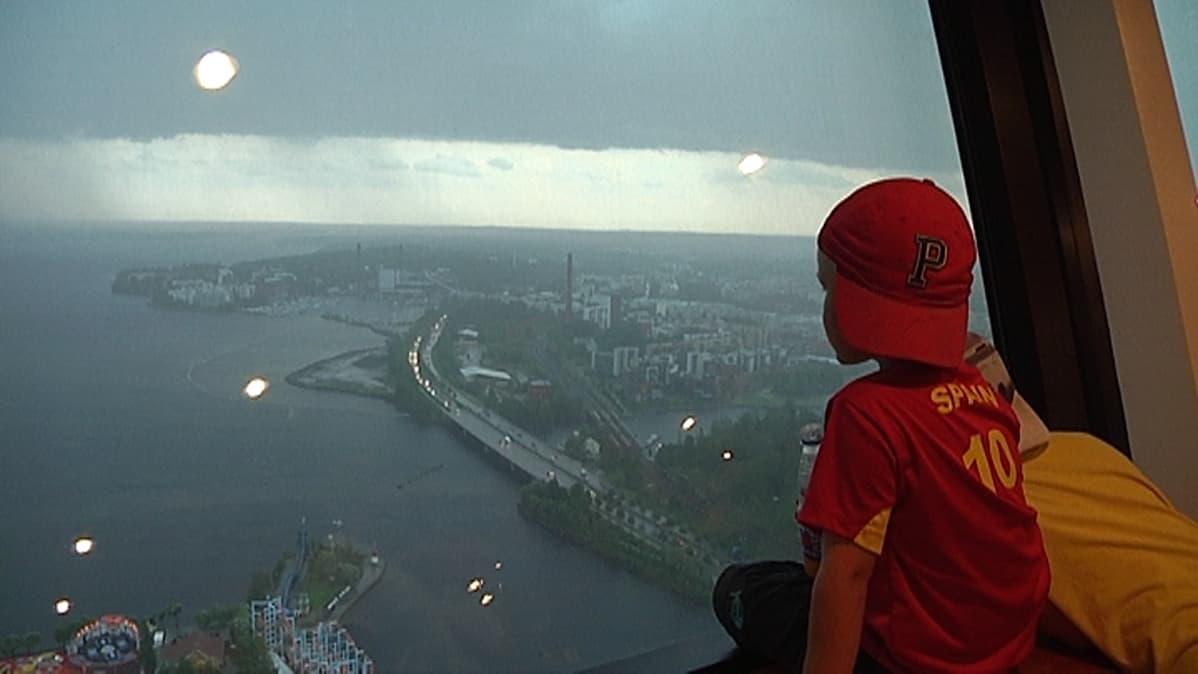 Poika katselee Näsinneulasta ukkosmyrskyä.