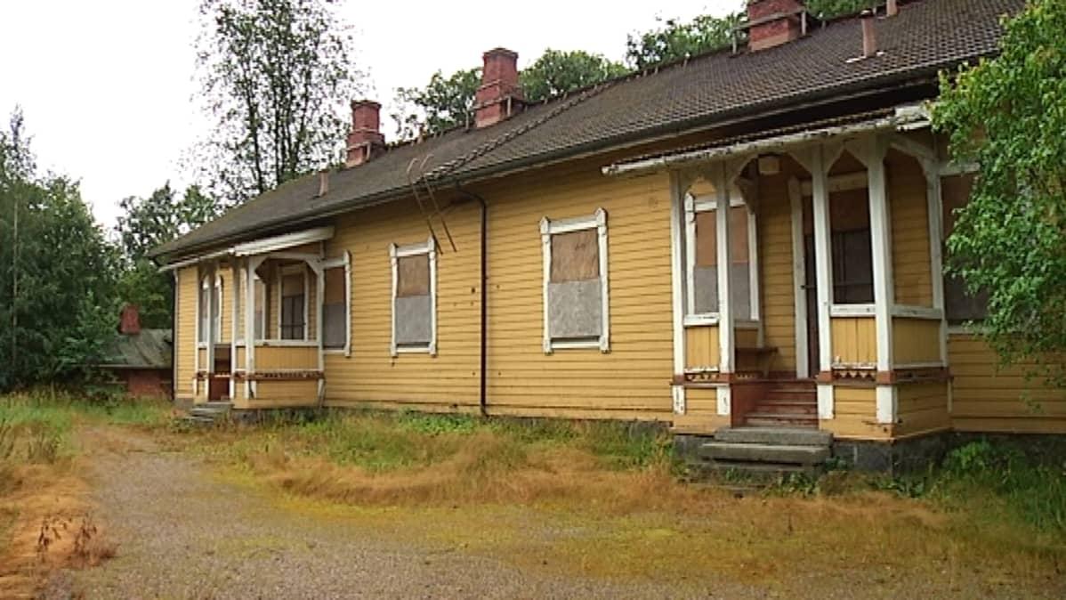 Entisessä rautatieläisten asuintalossa on ikkunat peitetty levyillä.