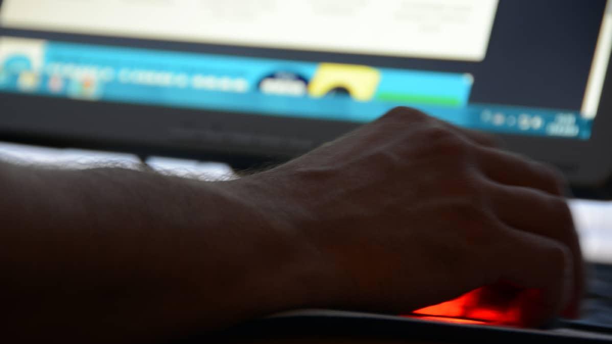 Kuvassa miehen käsi ja tietokoneen hiiri
