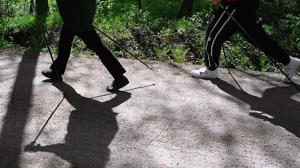 Sauvakävelijöitä metsätiellä.