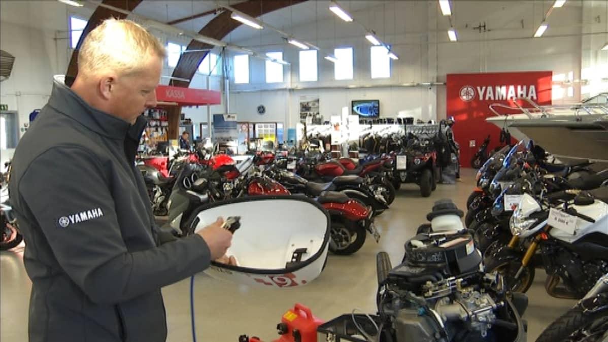 Yrittäjä Juha Kavalto suihkuttaa turvasiruja myös moottorin kannen alle