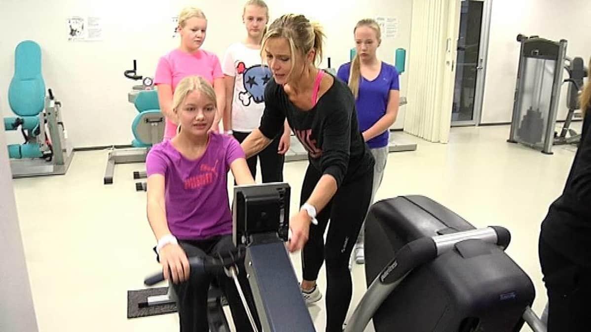 Liikunnanopettaja Päivi Putkuri opastaa Veera Mattilaa soutulaitteen käytössä