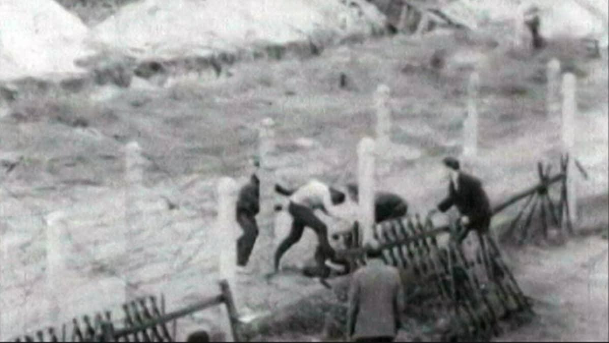 Ihmisiä pakenee Berliinin muurilla.