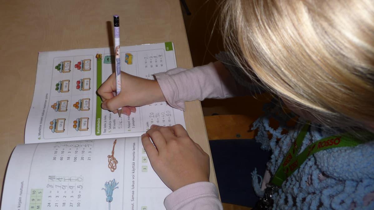 Tyttö tekee matematiikan läksyjä