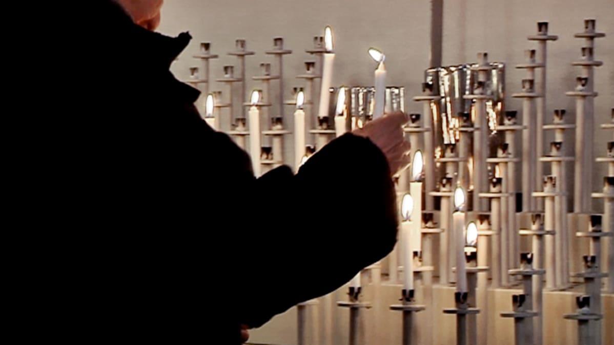 Nainen pitää kynttilää Kuopion tuomiokirkossa.