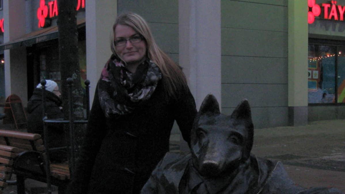 Nainen seisoo susipatsaan vieressä