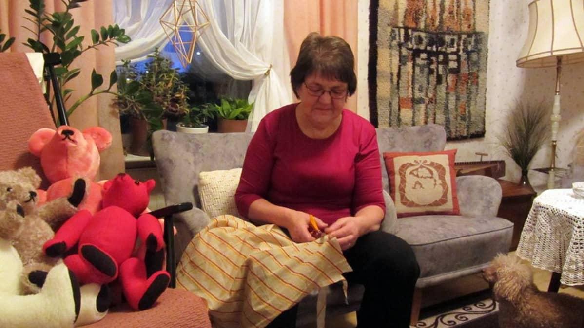 Kuvassa nainen leikkaa kankaasta kuteita.
