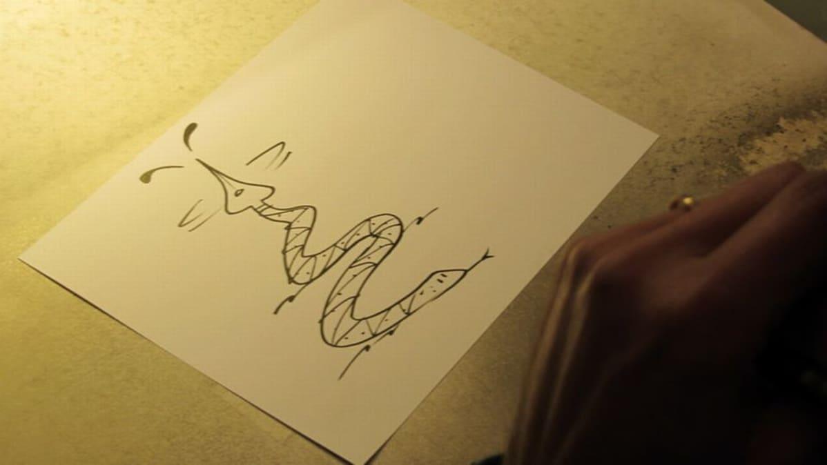 Kuva käärmeestä, jonka häntä on mustetta roiskuva mustekynän kärki.