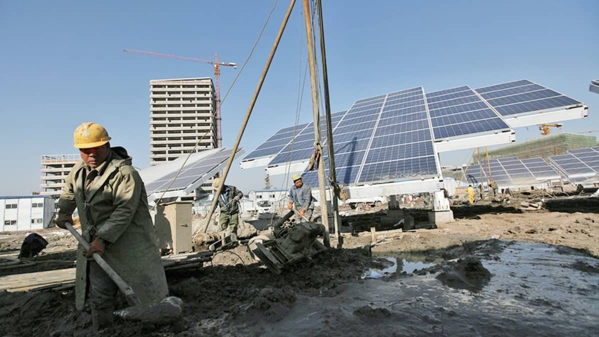 Kiinalaiset työntekijät pystyttävät valtavaa aurinkopaneelia Tianjinissa.