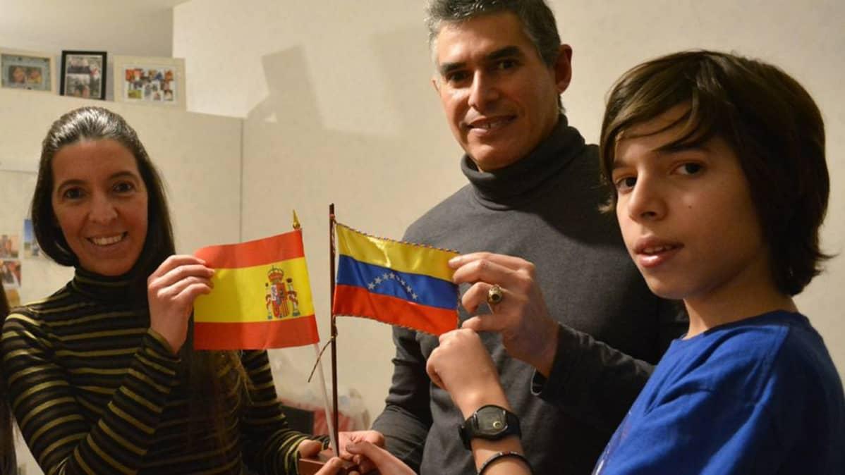 Venezuelesta Espanjaan ja sieltä Suomeen muuttanut perhe esittelee Espanjan ja Venezuelan lippuja.