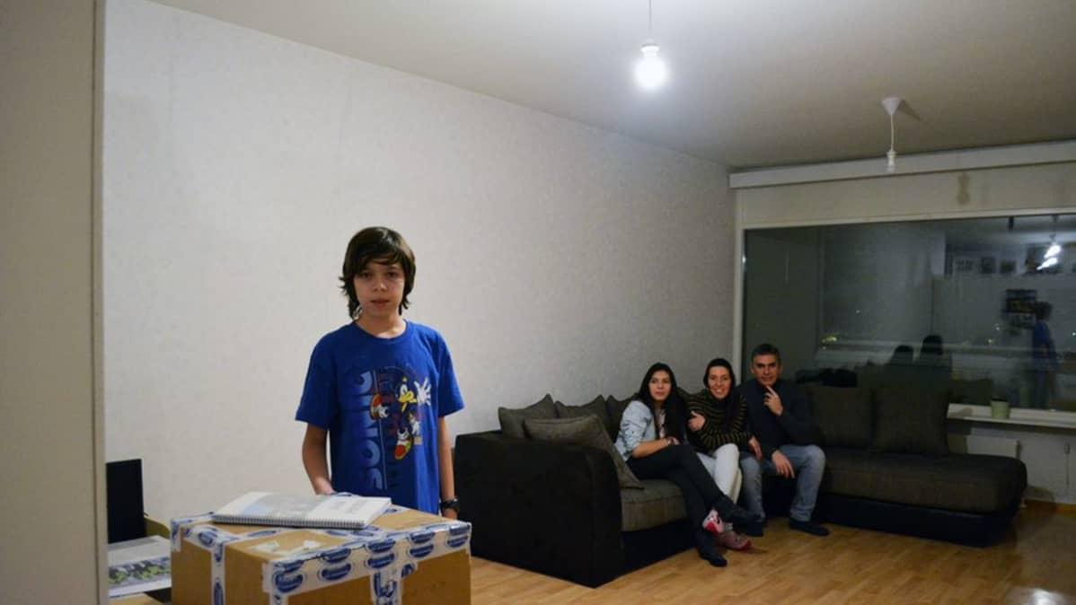 Venezuelesta Espanjaan ja sieltä Suomeen muuttanut nelihenkinen perhe uuden kotinsa vielä aika tyhjässä olohuoneessa.