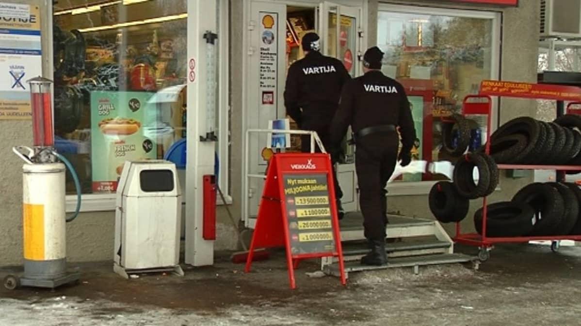 kaksi vartijaa kävelee sisälle huoltoasemalla.