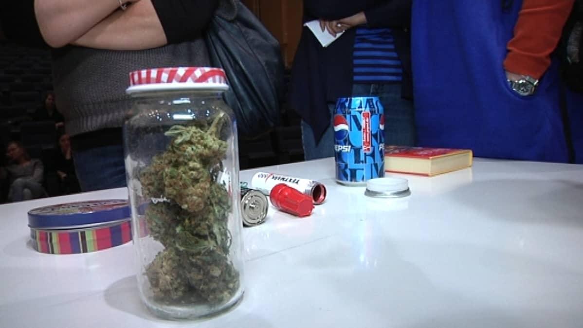 Pöydällä marihuanaa ja huumeidenkäyttövälineitä.
