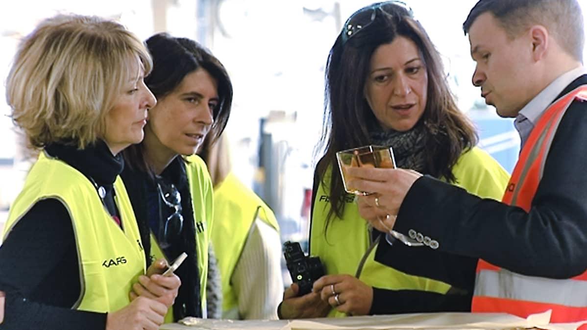Naistoimittajat keltaisissa Fiskarsin turvaliiveissä ihastelevat valmista lasiesinettä.