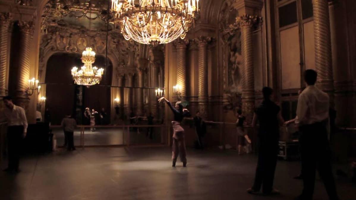 Balettitanssijat verryttelevät hetkeä ennen nousuaan Pariisin oopperan lavalle.