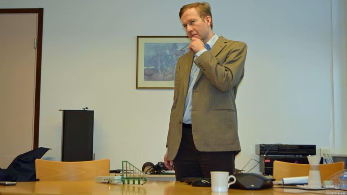 Tutkija Mikko Ahonen seisoo pöydän takana