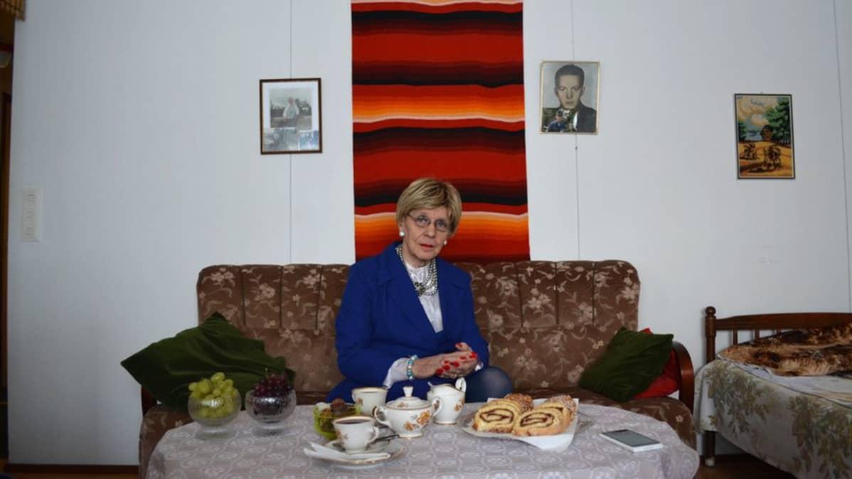 Ensio Nyman, Eveliina, istuu olohuoneessaan sohvalla, edessä pöydällä kahvikattaus.