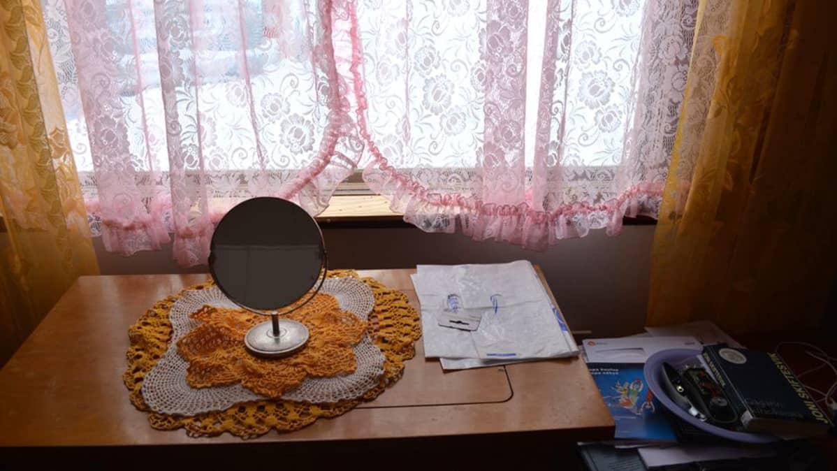 Pyöreä, pieni peili pöydällä, ikkunan edessä. Ikkunan eteen on vedetty pitsiverhot.