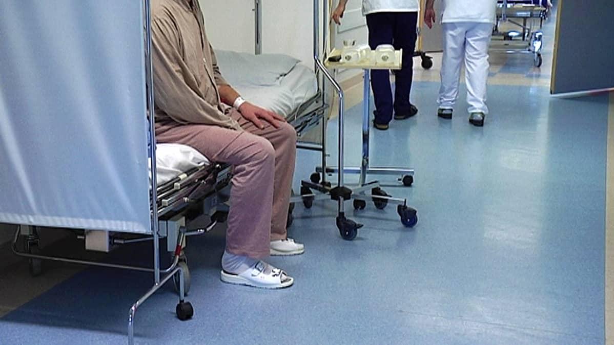 Potilas istuu vuoteella vuodeosaston käytävällä.