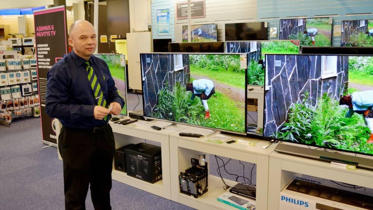 Teuvo Karhu esittelee televisioita elektroniikkamyymälässä.