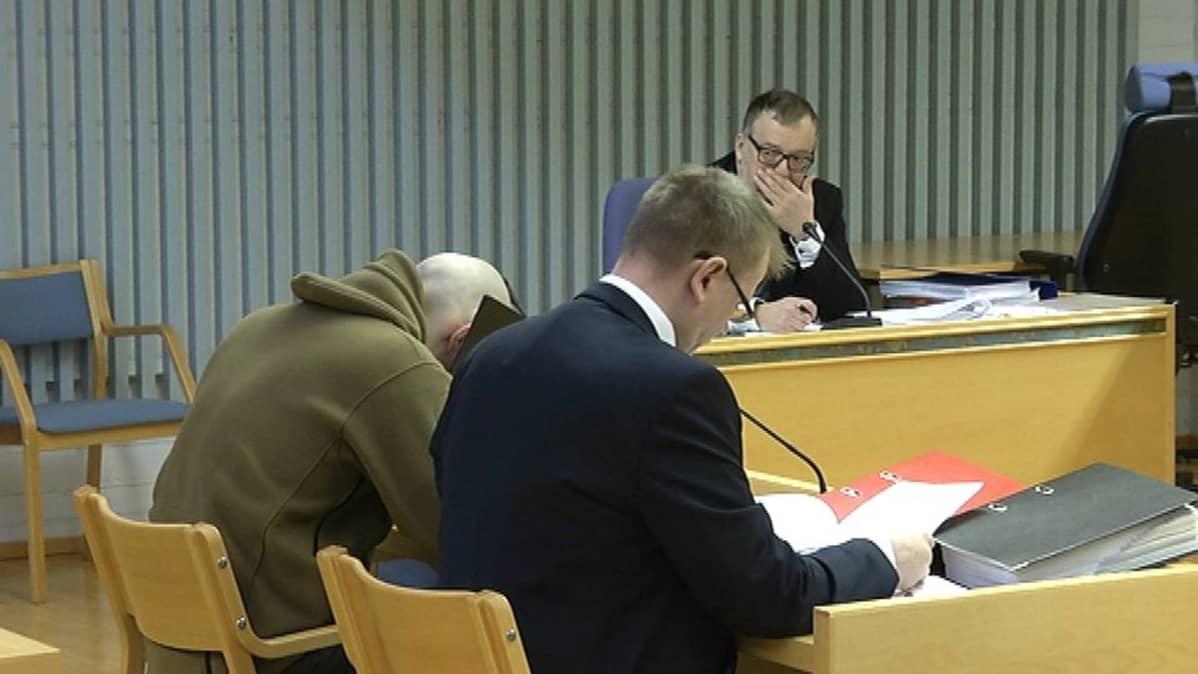 Syytetty istuu pää painuksissa oikeussalissa.