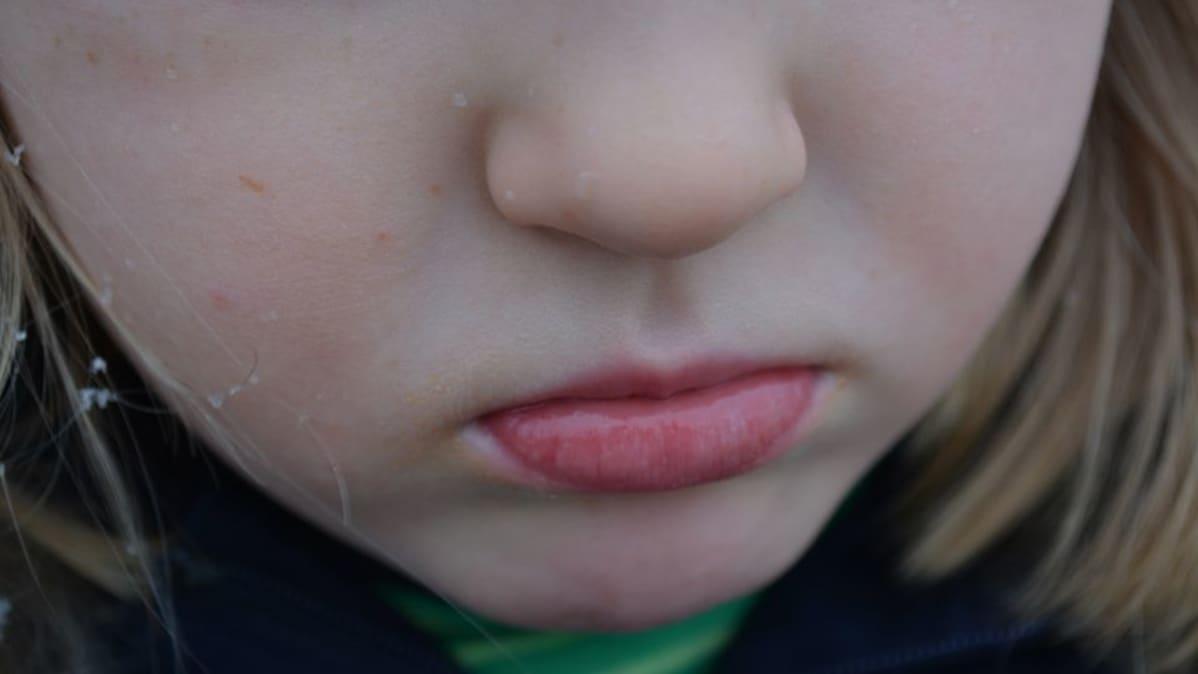 Lapsen kasvojen alaosa, murjottava suu.