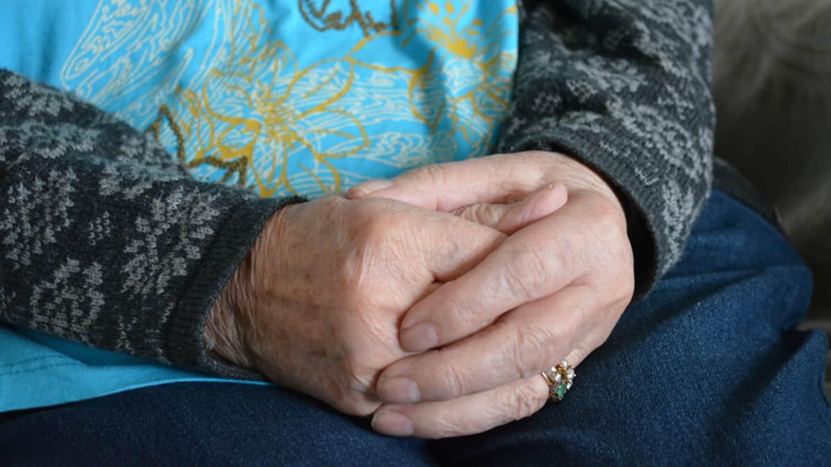 Vanhan ihmisen kädet ristittynä syliin.
