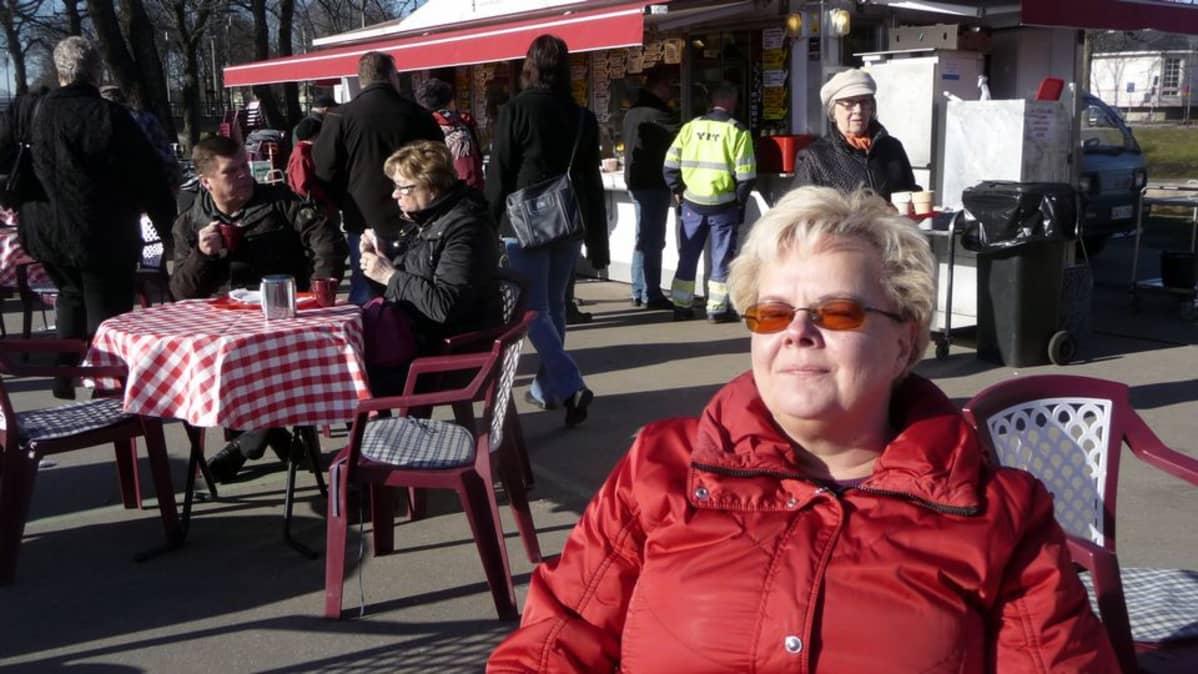 Seija Hotia-Klaavu nauttii auringonpaisteesta torilla.